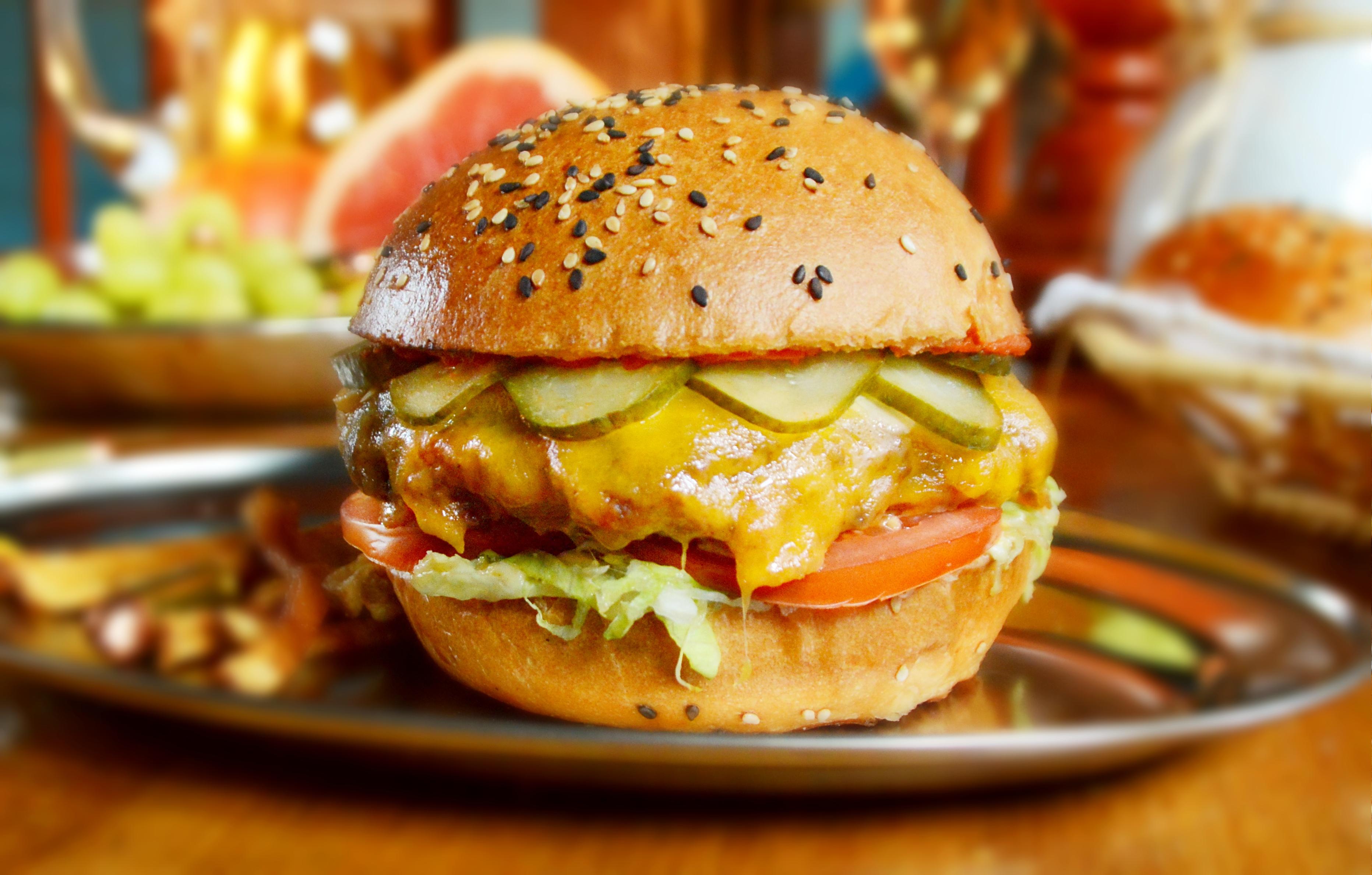 CHEESEBURGER Máslova houska z Pablovy rodinné pekárny, 150g mletého hovězího masa plněného bylinkovým máslem, anglický chedar, medově-hořčičná omáčka, tomatová omáčka, nakládaný okurek ve sladkokyselém nálevu, plátky rajčete, ledový salát 80,-